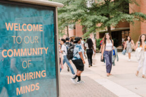 """photo of UMBC sign that reads """"Welcome to our community of Inquiring minds"""""""